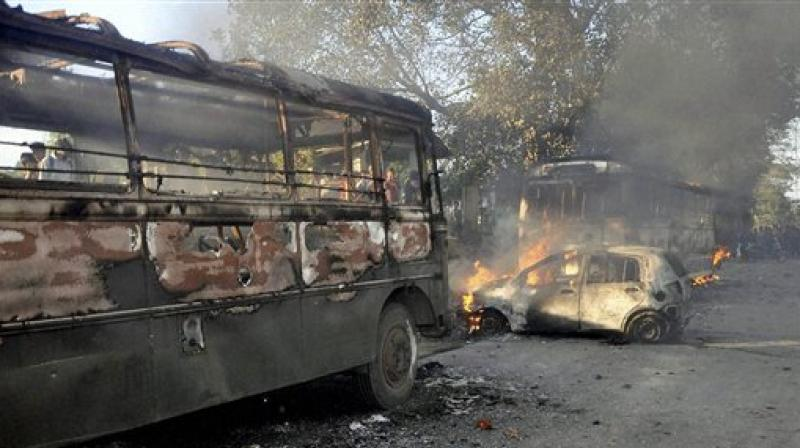 Angry people set on fire vehicles in Imphal East district on Sunday in protest against the United Naga Council (UNC)'s indefinite economic blockade. (Photo: PTI)