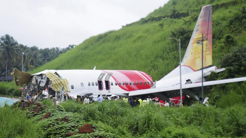 Officials stand on the debris of the Air India Express flight that skidded off a runway while landing in Kozhikode. (PTI)