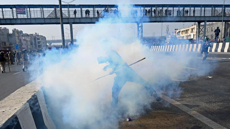 A farmer throws back a tear gas shell towards police during a tractor rally as farmers continue to protest against the central government's recent agricultural reforms in New Delhi on January 26, 2021. (AFP)