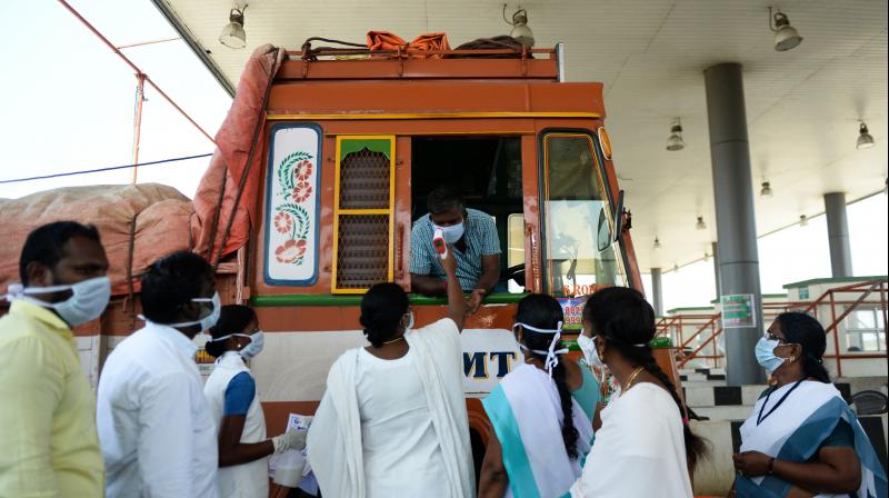 Health workers subject a truck driver to thermal screening at the Tamil Nadu-Andhra Pradesh interstate border on the outskirts of Chennai on March 24, 2020. (AFP)