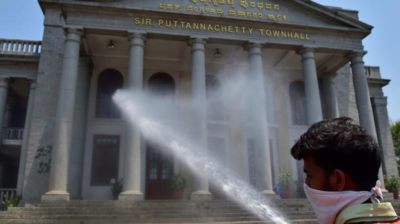 A civic worker direct a jet of sodium hypochloride on prominent buildings in Town Hall in Bengaluru as part of efforts to arrest the spread of the coronavirus Covid-19 on Martch 24, 2020. (DC Photo: Satish B)