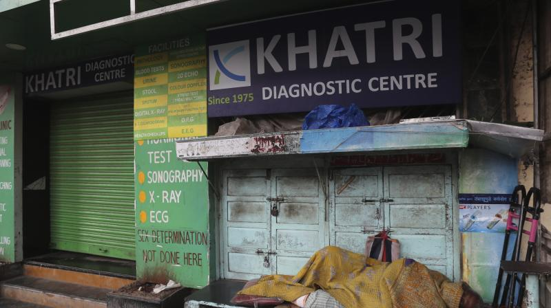 A homeless man sleeps outside a closed diagnostic centtre in Mumbai, on March 25. (AP)