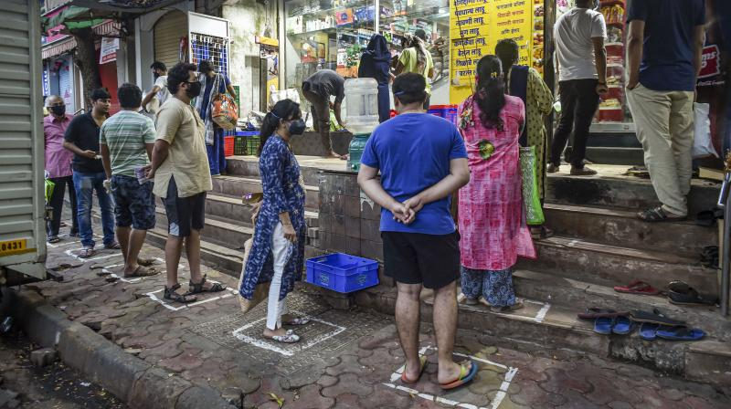 Customers stand within well-marked areas to maintain social distance as they wait outside a grocery on day one of the 21-day nationwide lockdown to contain the coronavirus pandemic in Mumbai on March 25, 2020. (PTI)