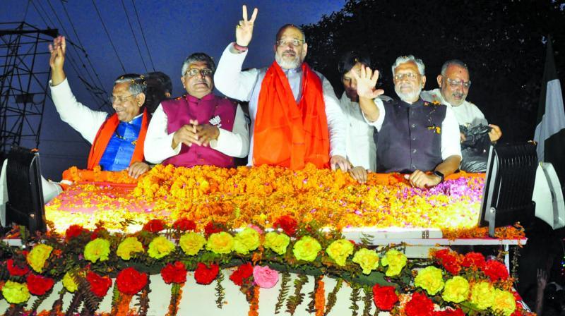 BJP president Amit Shah with Sushil Kumar Modi and party's Patna Sahib candidate Ravi Shankar Prasad during a roadshow in Patna on Saturday. (Photo: PTI)
