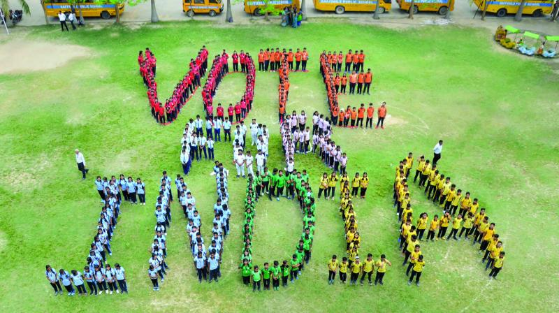 Students create a formation to raise awareness about voting rights ahead of the sixth phase of Lok Sabha polls in Mirzapur. (Photo: PTI)