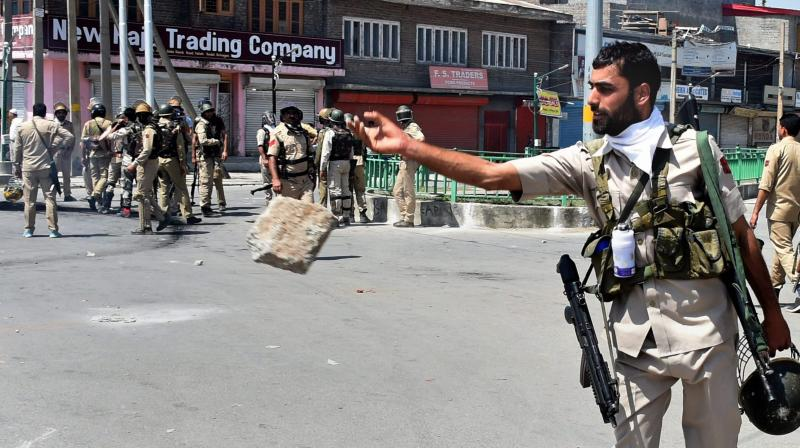 Policemen stands guard after a clash with the protesters in Srinagar on June 2. (Photo: PTI)
