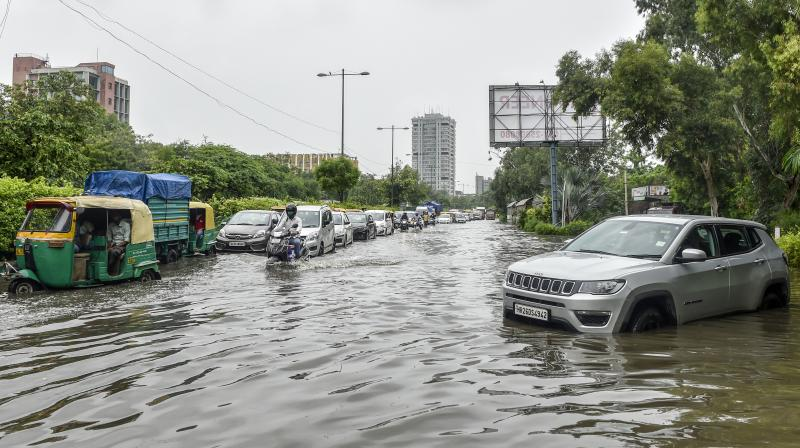 Commuters wade through a waterlogged Ring Road in New Delhi, Tuesday, July 27, 2021. (PTI /Ravi Choudhary)