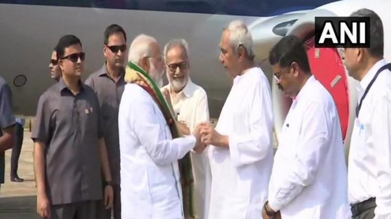 The PM is received by Governor Ganeshi Lal and Chief Minister Naveen Patnaik. (Photo: ANI)
