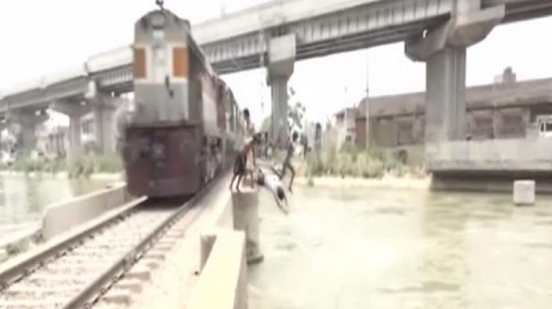Whenever a train approaches, these children climb railways track and jump into a nearby canal, throwing caution out of the window. (Photo: ANI)