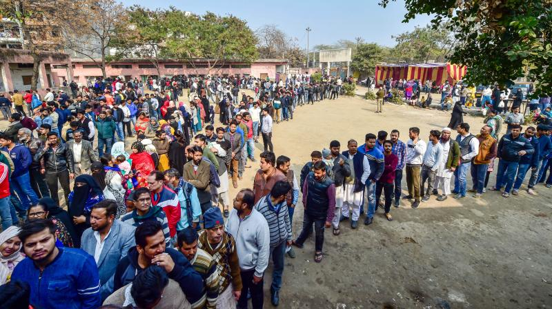 Voters wait in queues outside the Abul Kalam Azad school polling station in Shaheen Bagh area, which has been witnessing a peaceful protest against the Citizenship Act for several weeks, during the Delhi Assembly elections, in New Delhi. PTI photo