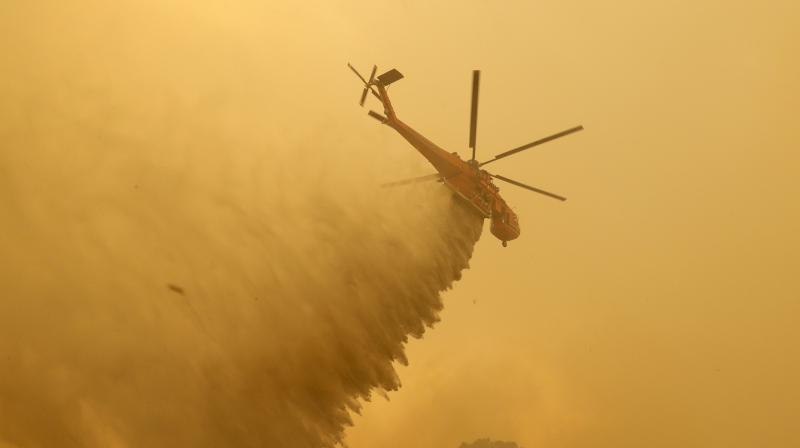 File photo shows a helicopter drops water on a fire near Bumbalong, south of the Australian capital,Canberra. AP photo