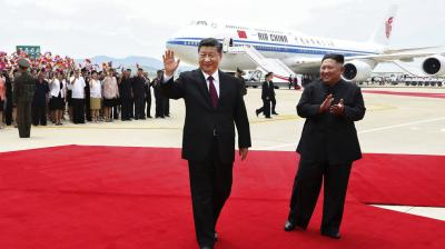 Chinese President Xi Jinping, left, waves next to North Korean leader Kim Jong-un as he arrives at the Sunan International Airport in Pyongyang, North Korea. (Photo: AP)