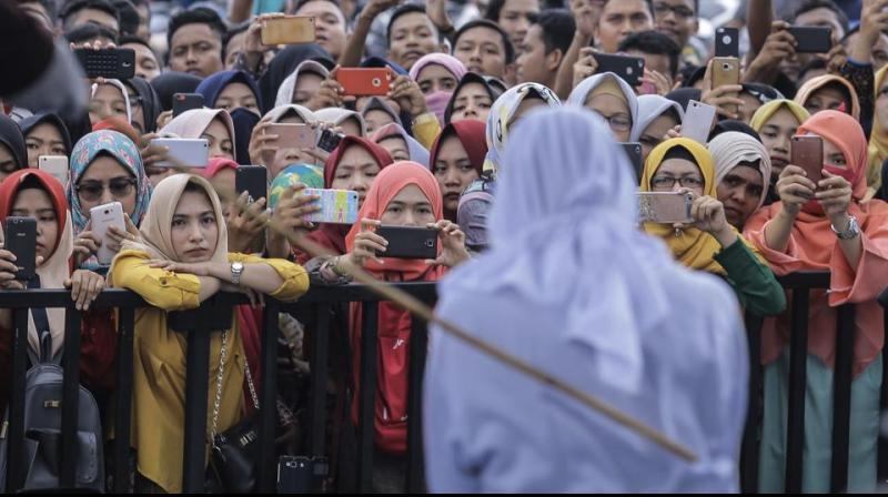 People use their mobile phones to take pictures as a Sharia law official whips a woman who is convicted of prostitution during a public caning outside a mosque in Banda Aceh. (Photo: AP)