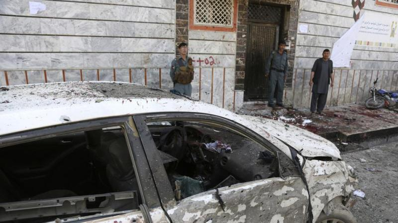 Afghan police stand outside a voter registration centre which was attacked by a suicide bomber in Kabul, Afghanistan.(Photo:AP )