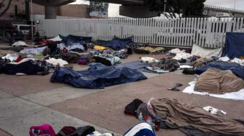 Central American migrants travelling in the 'Migrant Via Crucis' caravan sleep outside 'El Chaparral' port of entry to US. (Photo:  AFP)