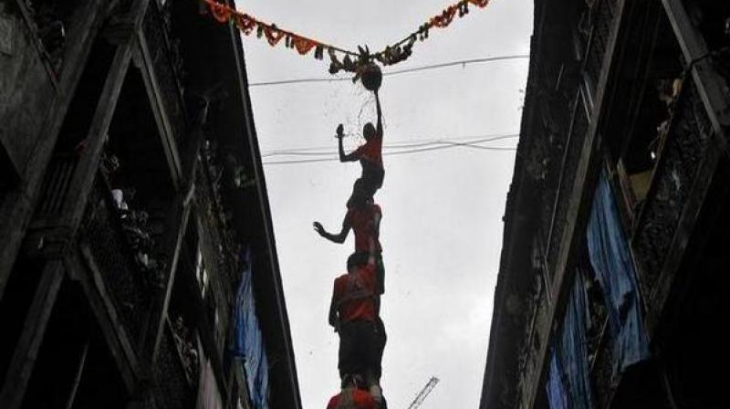 The Dahi-Handi ritual is part of the Janmashtami festival in the state in which youngsters (called Govindas), dressed in colourful costumes, make a human pyramid to reach the earthen pot having buttermilk, suspended in mid-air, and break it. (Photo: ANI)