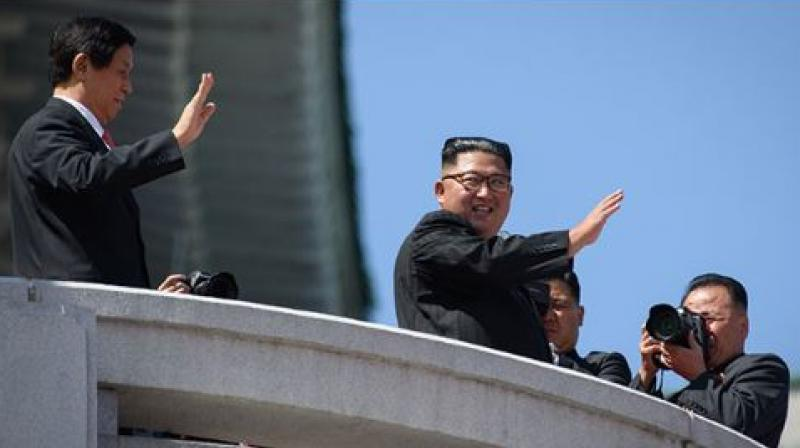 Kim Jong Un showed off his friendship with China, raising the hand of President Xi Jinping's envoy as they saluted the crowd together afterwards (Photo: AFP)