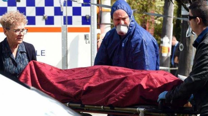 Forensic police (C) and other officials remove a dead body from the crime site in the suburb of Australia's western city of Perth on September 10, 2018. (Photo: AFP)