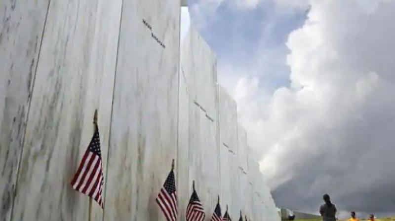 Visitors to the Flight 93 National Memorial pause at the Wall of Names honouring 40 passengers and crew members of United Flight 93 killed when the hijacked jet crashed at the site during the 9/11 terrorist attacks, near Shanksville, Pennsylvania. (Photo: AP)