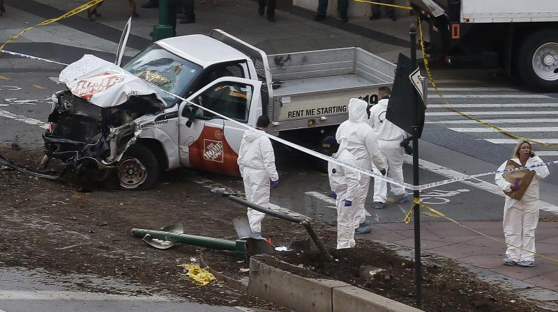 Authorities stand near a damaged Home Depot truck after a motorist drove onto a bike path near the World Trade Center memorial, striking and killing several people in New York. (Photo: AP)