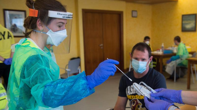 Volunteers of the 'Detente y Ayuda' (Stop and Help) DYA non-profit organization in protective gear take samples from fishermen, before putting out to sea, at a COVID-19 disease testing centre at the seaport of the Spanish Basque city of Hondarribia. (AFP)