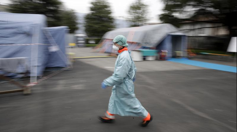 A worker wearing a mask and protective gear walks between the emergency structures set up to ease procedures at the Brescia hospital in northern Italy. As Italy prepares to emerge from the West's first and most extensive coronavirus lockdown, it is increasingly clear that something went terribly wrong in Lombardy, the hardest-hit region in Europe. (AP)