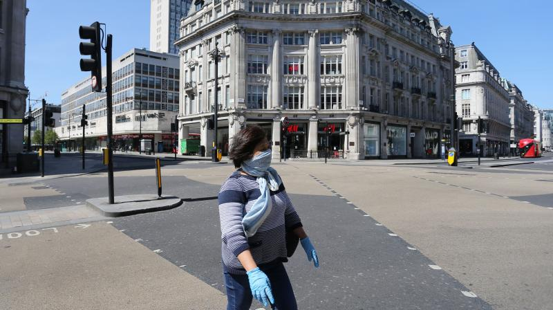 A woman wearing PPE crosses an empty road at Oxford Circus, London. (AFP)