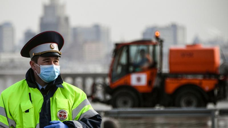 A Russian traffic police officer wearing a face mask and protective gloves stands in front of a municipal vehicle cleaning and disinfecting a street at Vorobyovy Hills observation point in Moscow. (AFP)