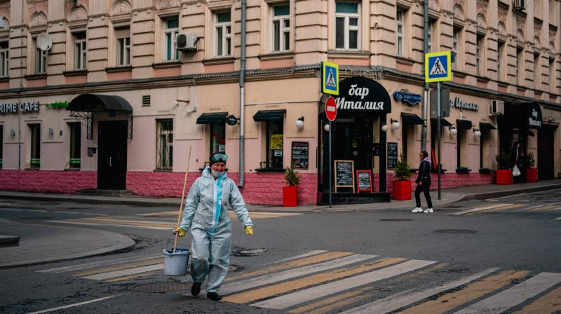 A communal worker who disinfects residential buildings crosses a street in Moscow. (AFP)