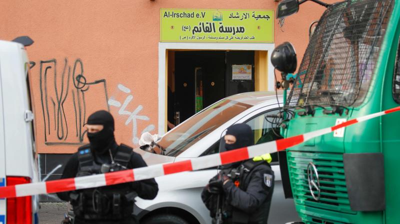 Poilice stand in front of Al-Irschad Mosque during a raid today. (AFP)