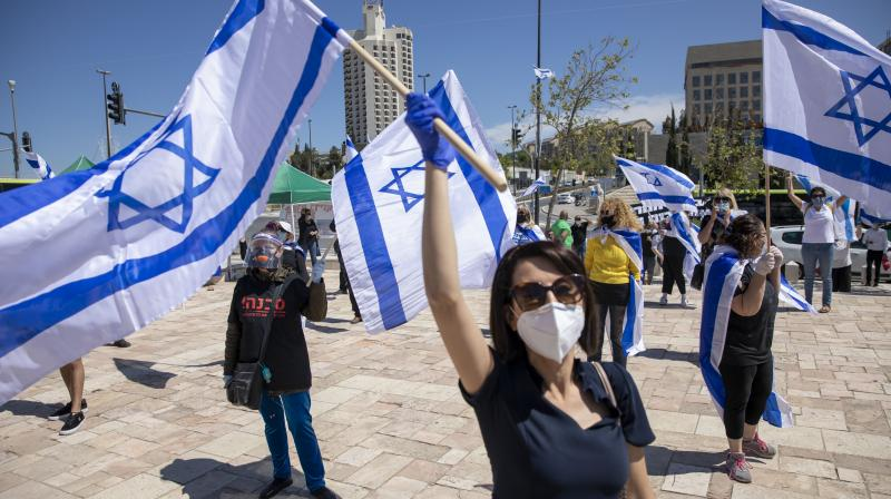 Protesters wearing masks and gloves amid concerns over the country's coronavirus outbreak hold Israeli flags and shout slogans during a protest by supporters of Prime Minister Benjamin Netanyahu in front of Israel's Supreme Court in Jerusalem. (AP)