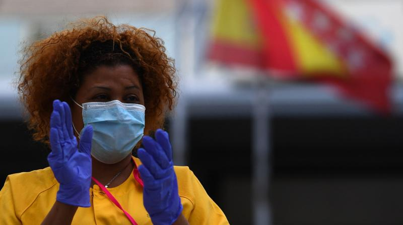 A healthcare worker applauds in return as she and her colleagues are cheered on outside the Gregorio Maranon Hospital in Madrid. (AFP)