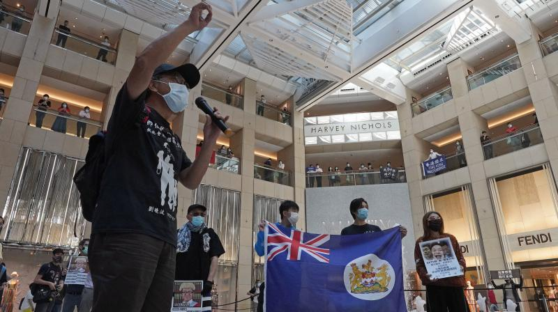 Pro-democracy protesters wearing face mask raise a Hong Kong colonial flag during a protest at a shopping mall in Hong Kong.(AP)