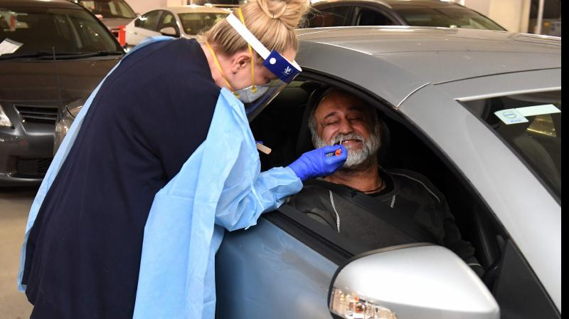 Medical staff perform a test for the COVID-19 coronavirus on a driver at a drive-through testing site in a Melbourne carpark. (AFP)