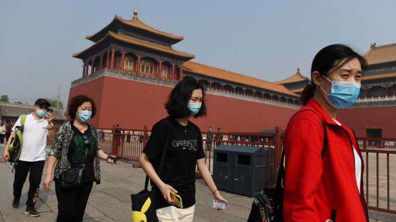 People wear face masks amid concerns of the COVID-19 coronavirus as they walk to the entrance of the Forbidden City, the former palace of China's emperors, in Beijing. (AFP)
