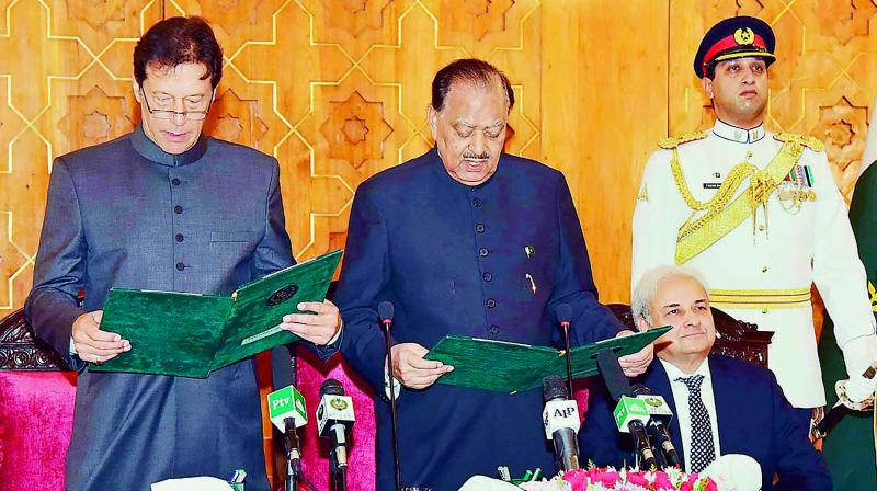President of Pakistan Mamnoon Hussain (center) takes an oath from newly-appointed Prime Minister Imran Khan (left) during a ceremony in Islamabad, as caretaker Prime Minister of Pakistan Nasirul Mulk (second right) looks on. (Photo: AFP)