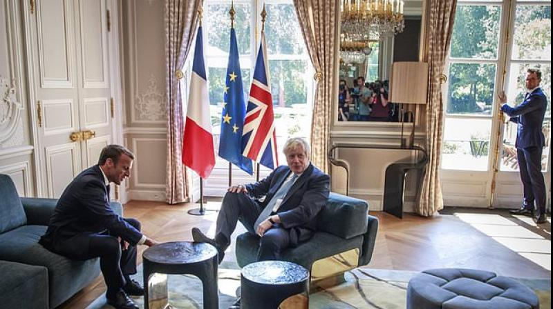 British Prime Minister Boris Johnson may have taken a month to embark on his first trip abroad, but he was quick to make himself at home in President Emmanuel Macron's gilded palace, putting his feet up on the furniture. (Photo: AP)