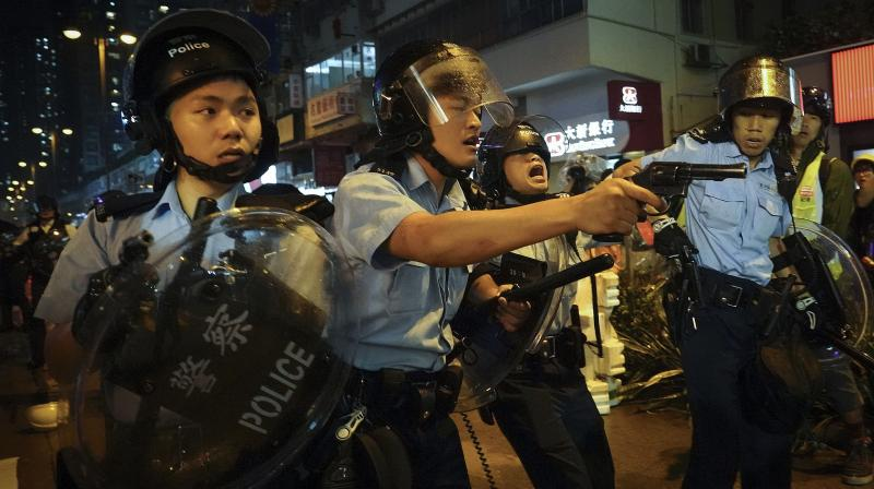 Officers pulled their guns after a group of remaining protesters chased them down a street with sticks and rods, calling them 'gangsters.' The officers held up their shields to defend themselves as they retreated. (Photo: AP)