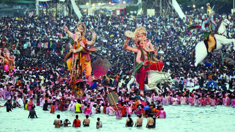 Devotees throng to the beach on last day of Chaturthi.