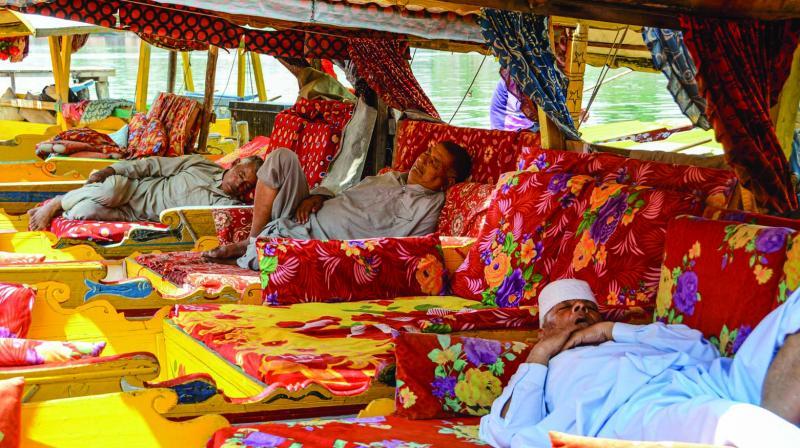 Shikara owners sleep in their parked shikaras at an empty Dal Lake in Srinagar on Saturday. (Photo: PTI)