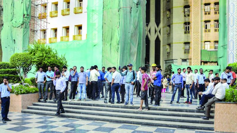 People come out of an office building at Connaught Place during a tremor in New Delhi on Tuesday. (Photo: PTI)