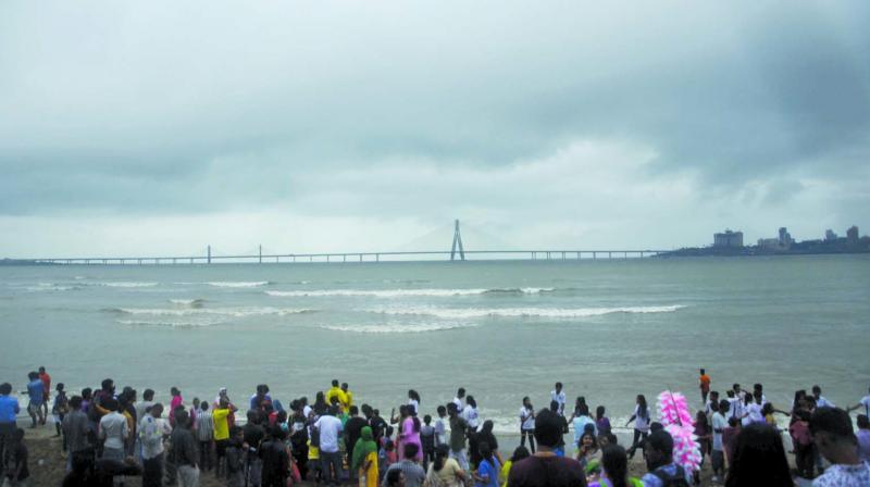 People enjoying the sight of black clouds at Juhu beach.