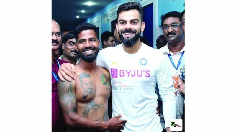 Virat Kohli poses with die-hard fan Pintu Behera, who has 14 tattoos on his body that highlight Kohli's career so far, in Visakhapatnam.