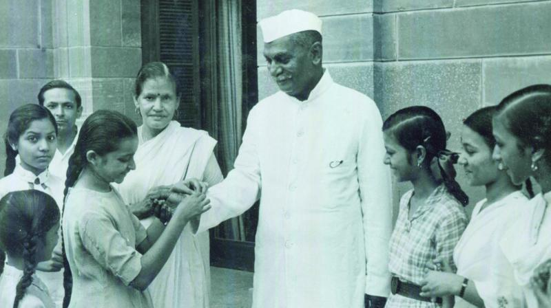 Schoolgirls tie a rakhi on India's first President, Dr Rajendra Prasad