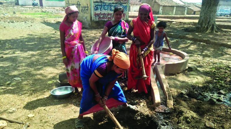 Women building a water bank near a hand pump in a Chhattisgarh village.