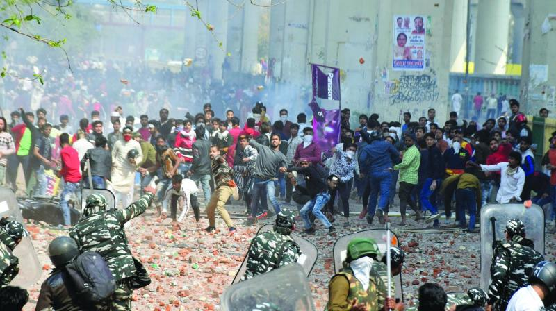 Protesters hurl brick, bats during clashes between police, a group of anti-CAA protesters and supporters of the new Citizenship Act at Jafrabad in New Delhi on Monday. (Photo: Asian Age)
