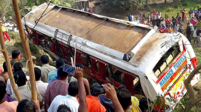People looking at a tourist bus which met with an accident near a steep curve at Dhauli hill in Bhubaneswar. (Photo: PTI)
