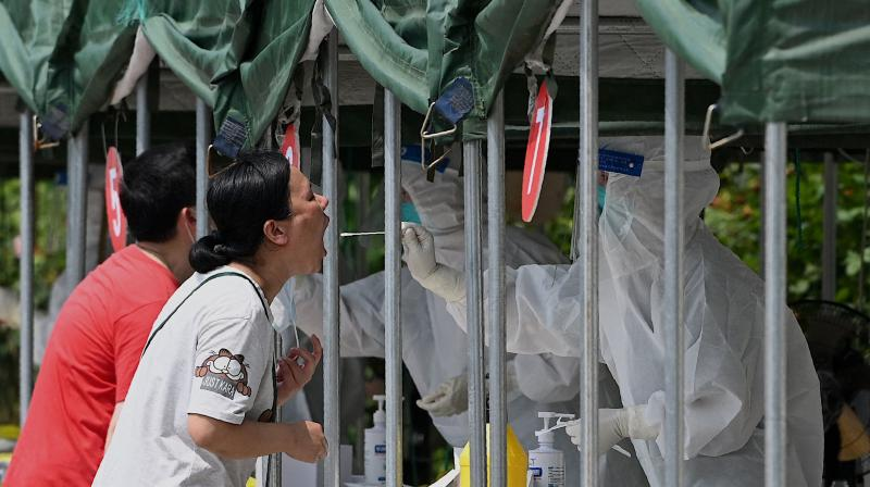 A health worker takes a swab sample from a woman to be tested for the Covid-19 coronavirus at a nucleic acid sample collection station at a park in Beijing on August 5, 2021. (Noel Celis / AFP)