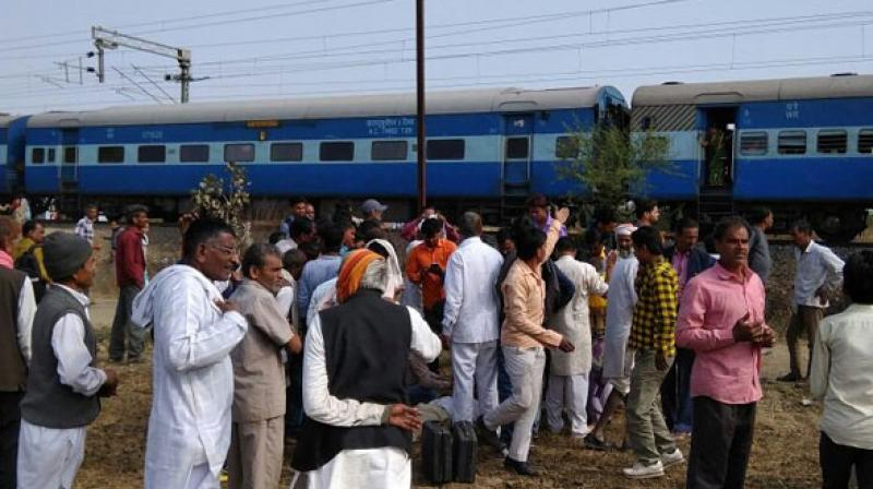 People gather around the train as it is brought to a halt. (Photo: Twitter)