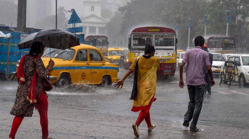 People cross a road during a heavy downpour in Kolkata on Thursday.